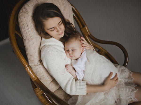 Мама с младенцем на руках сидит в кресле