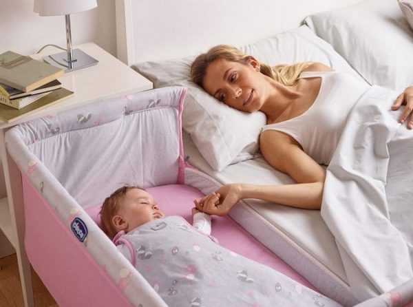 Мама дотрагивается до детской кроватки с младенцем, которая стоит вплотную ко взрослой кровати