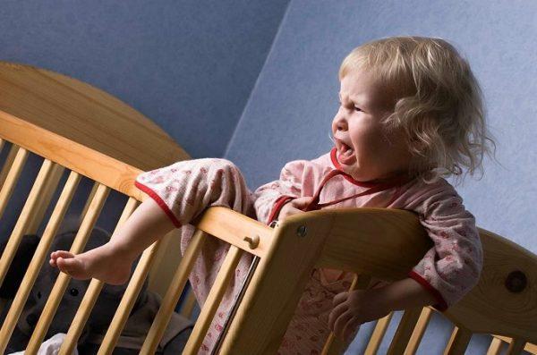 Девочка 1,5–2 лет плачет и пытается вылезти из кровати