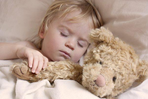 Ребёнок спит в обнимку с плюшевой игрушкой
