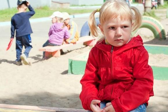 Грустная девочка сидит на лавочке, вдали играют другие дети