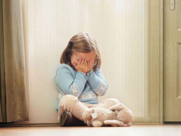 Девочка плачет дома, сидя на полу
