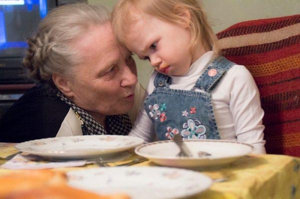 Бабушка рядом с внучкой за столом