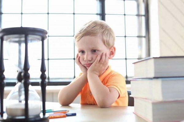 Мальчик с интересом смотрит на песочные часы