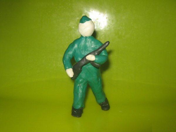Солдат шагает с автоматом в руках