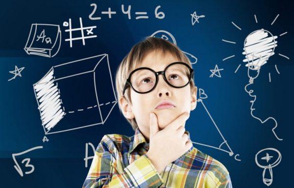 Мальчик стоит возле доски, на которой изображены кубы, примеры, лампочка, треугольник и пр