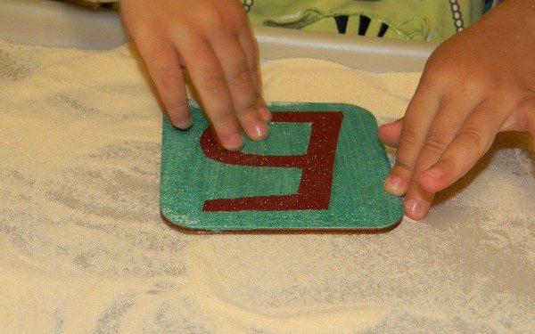 Ребёнок обводит пальцами шершавую букву, наклеенную на дощечку