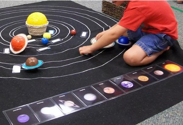 Мальчик выкладывает на ковре модель Солнечной системы