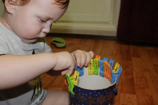 Ребёнок прикрепляет прищепки к краю широкого картонного цилиндра