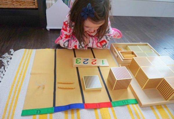 Девочка занимается с золотыми бусинами и числовыми карточками