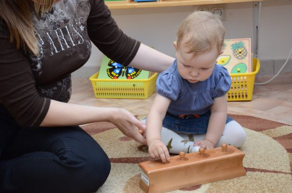 Мама с маленькой дочкой, девочка занимается с деревянным тренажёром