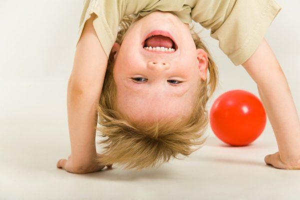 Ребёнок стоит на руках, рядом мячик