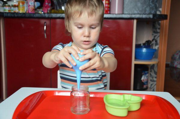 Мальчик переливает воду из формочки в стеклянную баночку с помощью спринцовки