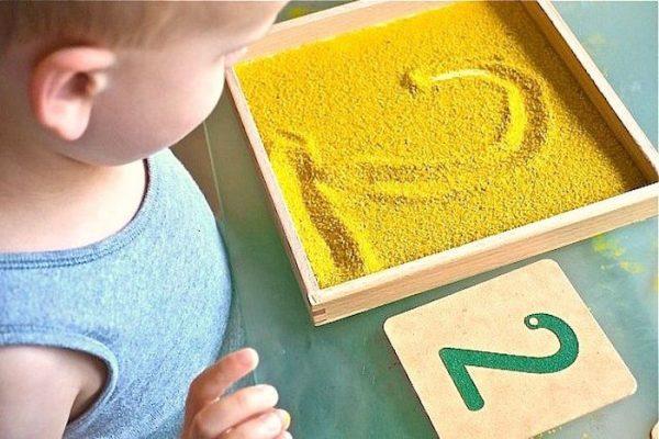 Мальчик нарисовал на песке цифру 2, рядом её изображение на деревянной дощечке