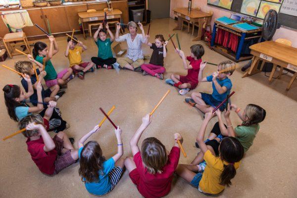 Педагог сидит в кругу с учениками, в руках у них палочки