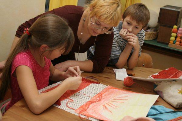 Девочка занимается рукоделием, педагог смотрит