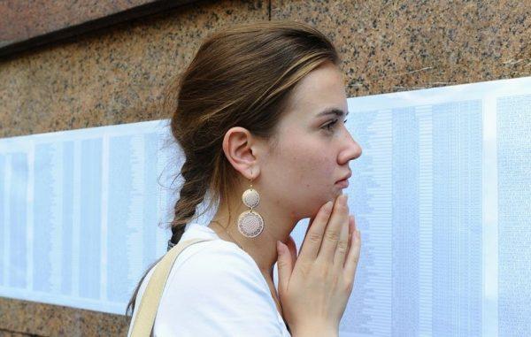 Девушка ищет себя в списках абитуриентов