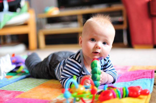 Малыш в полосатой футболке лежит на животике, перед ним яркие игрушки