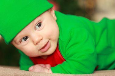 Малыш в зелёном костюме и шапочке лежит на животе