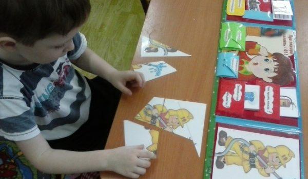 Мальчик составляет изображение из разрезных картинок