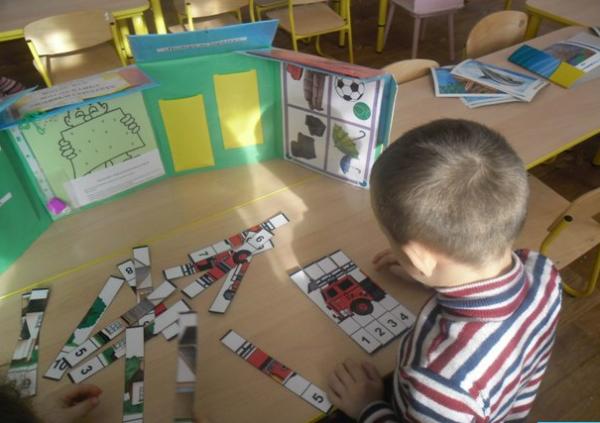 Мальчик складывает картинку из пронумерованных частей