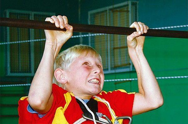 Мальчик с большим усилием подтягивается в спортивном зале